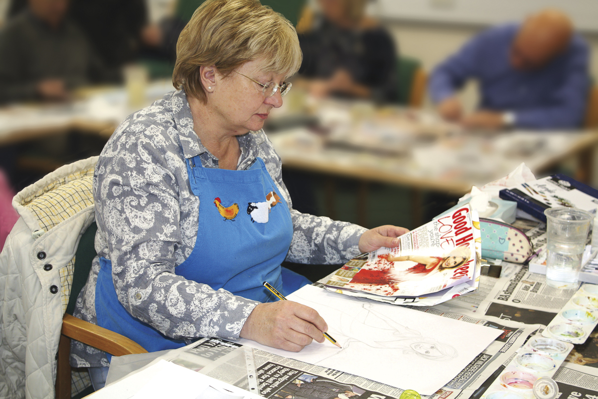 Woman in apron in front of table with a drawing