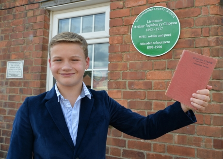 Student with Choyce's book of poetry in front of Green Plaque
