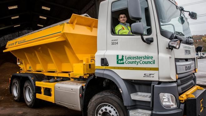 A person driving a gritting lorry