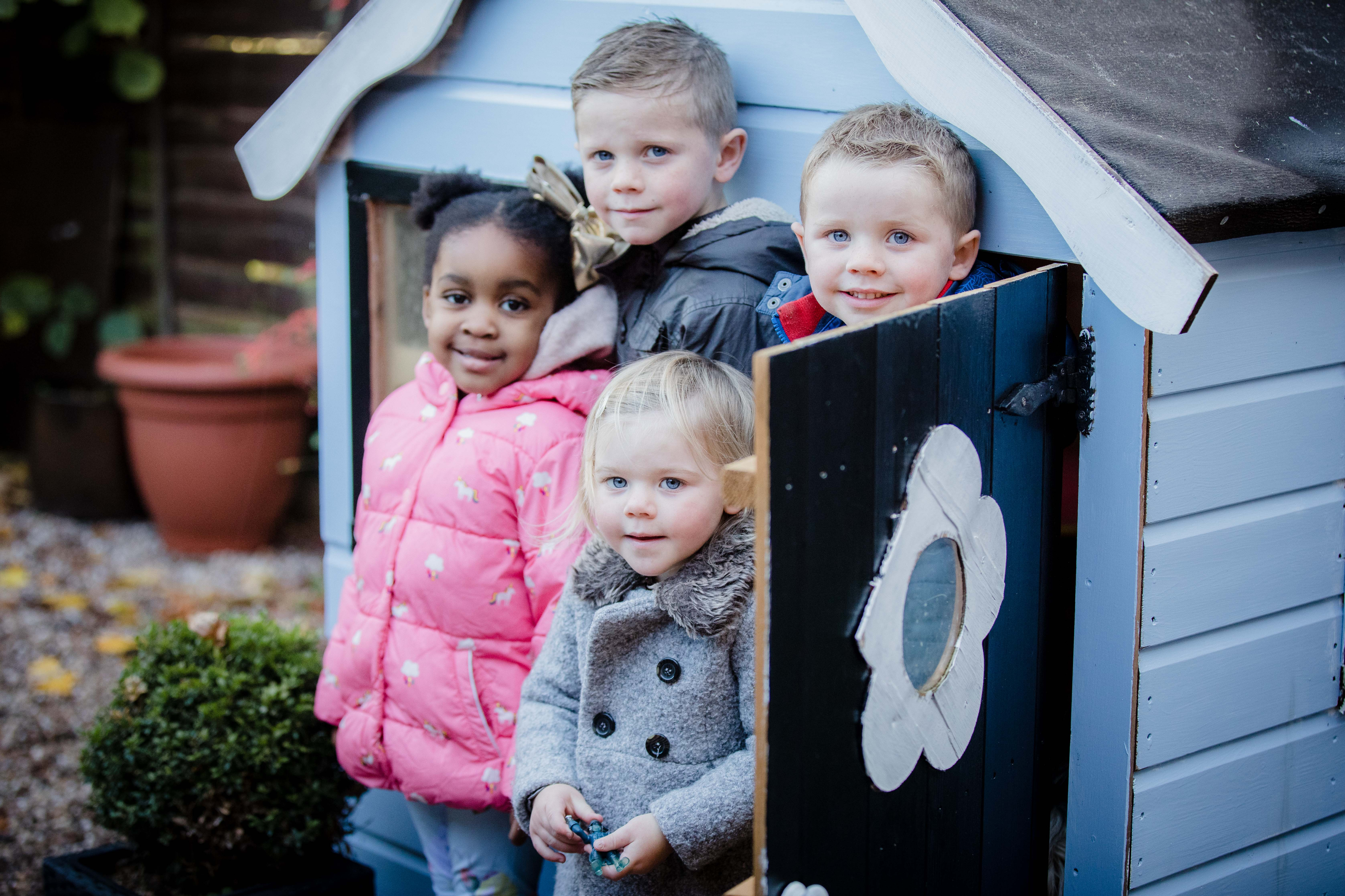 Children outside a play hut