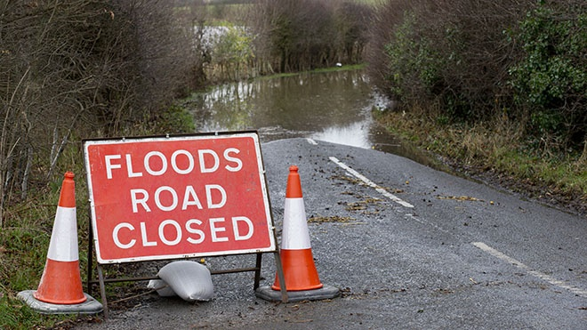 Flooded road with warning sign