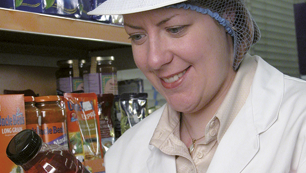 Woman wearing a white overall and hair net whilst inspecting some packaged food items