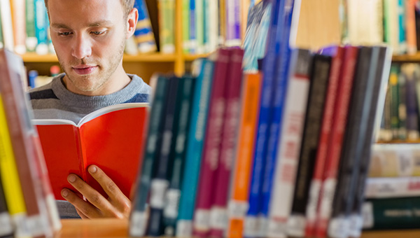 man reading a book in a library
