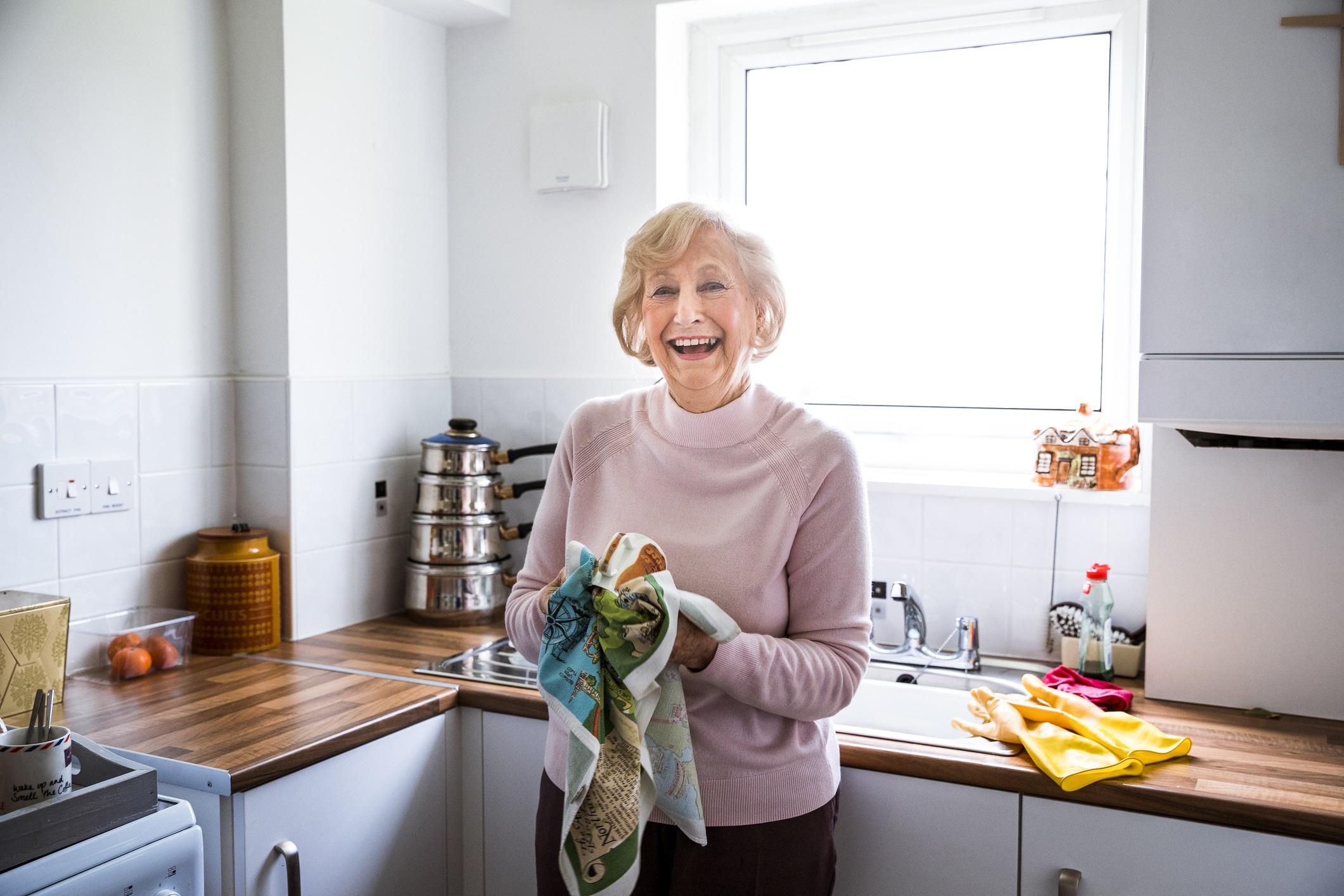 Senior lady laughing in kitchen