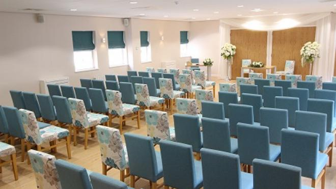 empty ceremony room with pale blue chairs