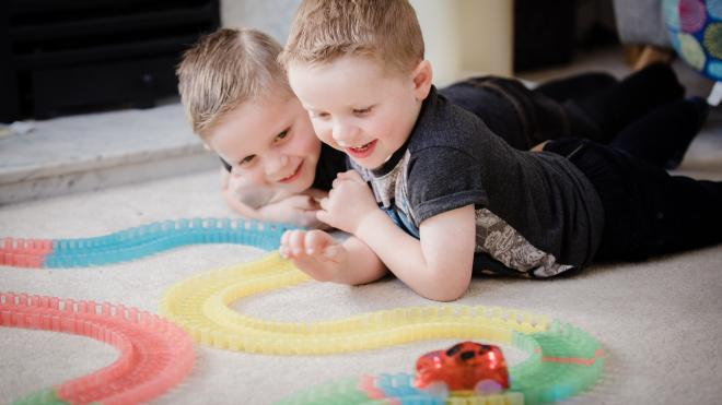 two boys playing with a train track