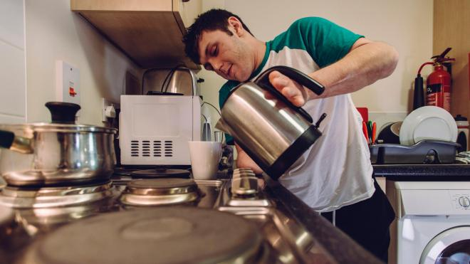 A young adult making a cup of tea