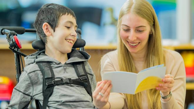 Woman reading book to disabled child in wheelchair
