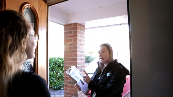 Cheerful woman answers door to person conducting survey