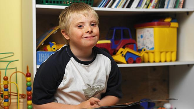 Young boy in front of bookcase at school