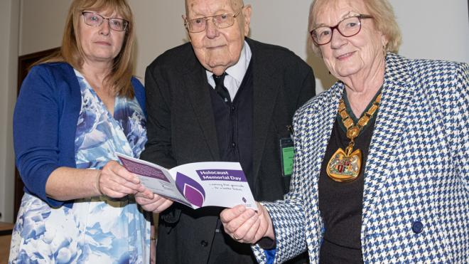 three people hold the service guide to county hall's holocaust memorial event