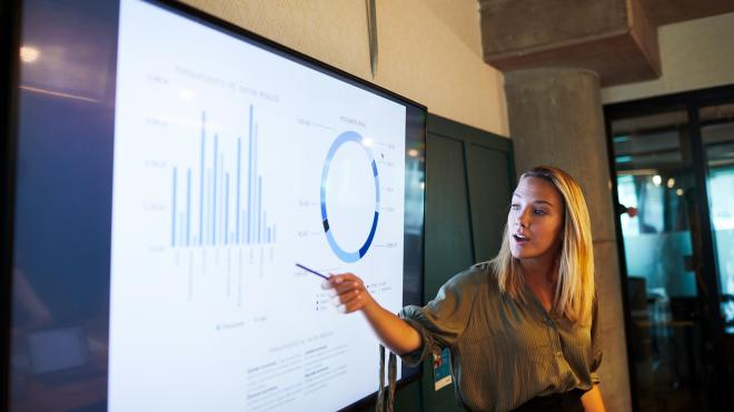 business woman pointing at graph on wall
