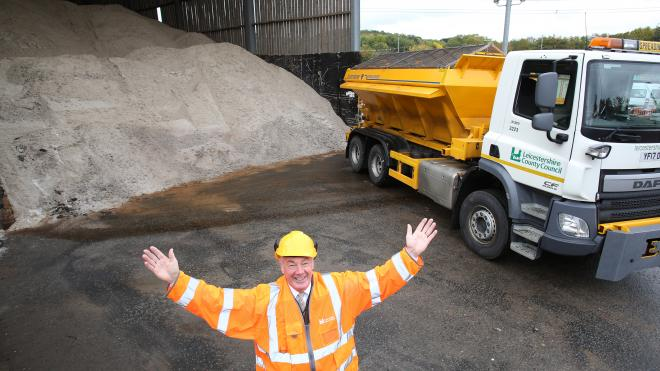 Man in highvis and helmet infront of a gritting lorry and a big pile of gritting salt