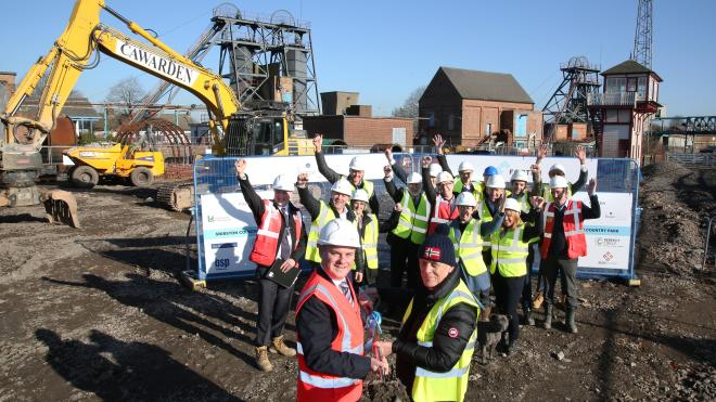 Group of people stand on the former Snibston Colliery site with shovels with building works behind them