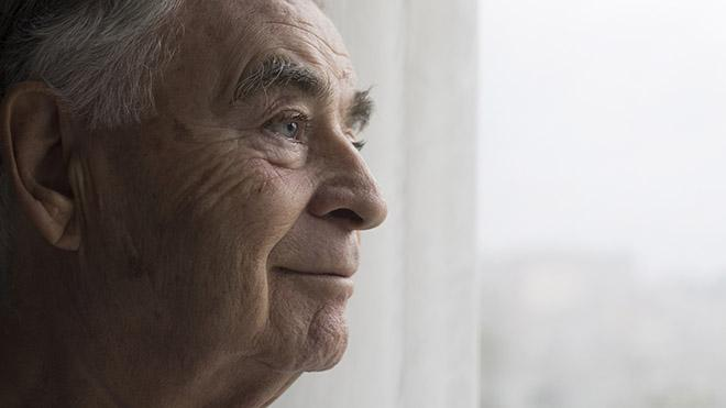 Older person looking out of a window