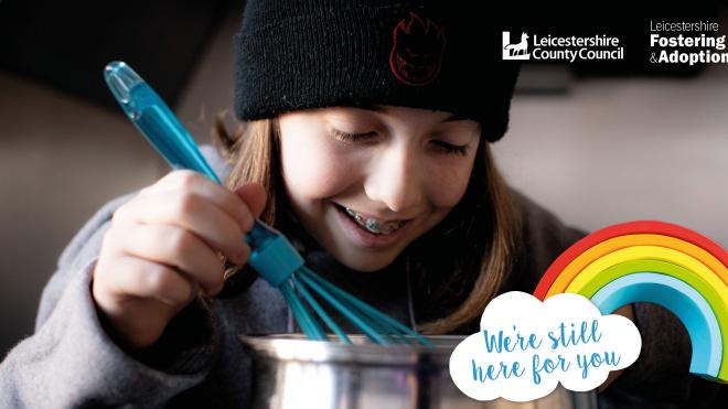 Girl wearing a black woolly hat stirring food in a saucepan with a whisk
