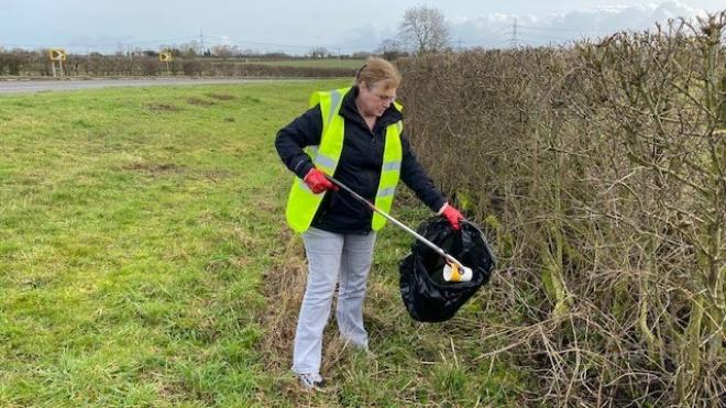 photo of lady in high vis litter picking by the side of the road