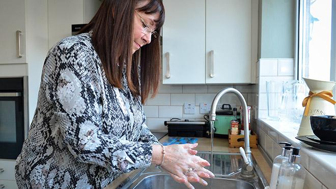 woman washing her hands with soap in the kitchen sink