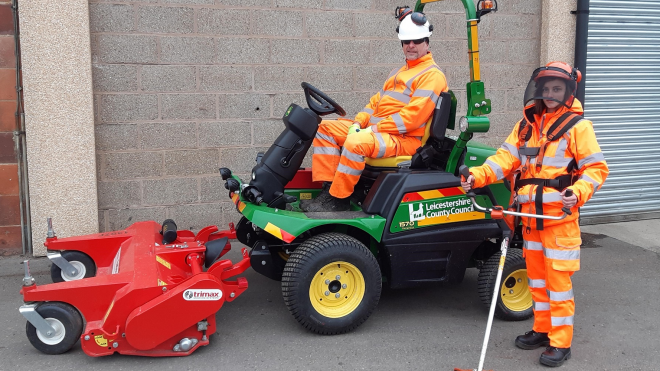 Photo of two people in safety gear and grass cutting equipment