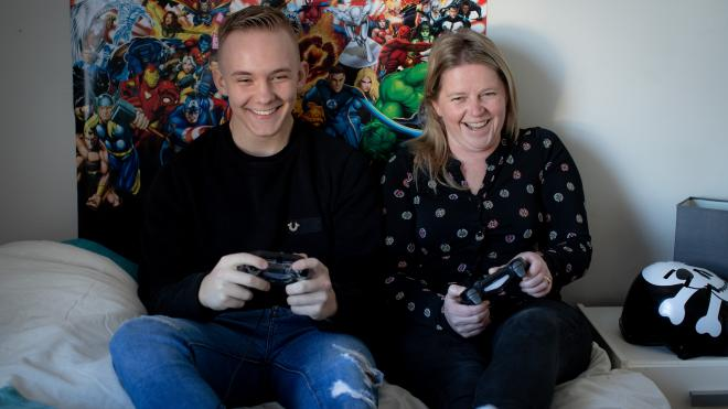 An older teenager playing a video game with his foster carer / adopter
