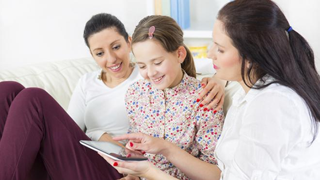 two ladies who are foster carers, and the girl they are fostering, are all looking and smiling at a tablet device