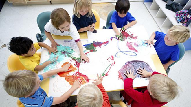 aerial view of children painting whilst sat around a table