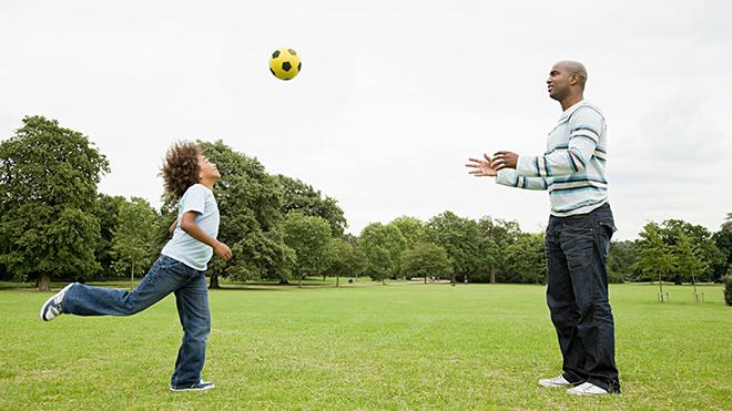 Child and adult playing football in a park