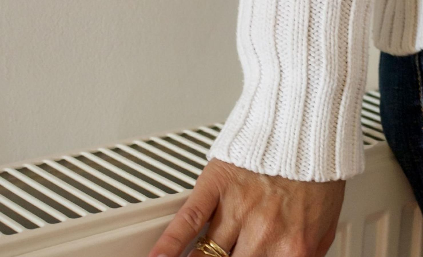 Person warming up next to a radiator