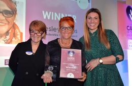 Three women stand on stage with the award winner holding her certificate and trophy