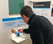 Member of the public taking a coronavirus test in Wigston Fields test centre