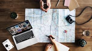 Planning holiday with a map and laptop
