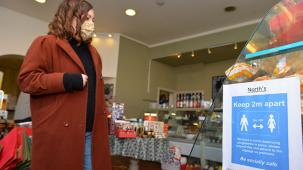 woman with face mask on social distancing in shop