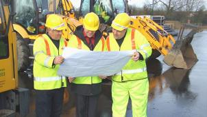 Road workers reading a map
