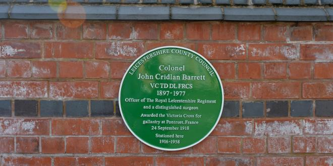 Green plaque on wall honouring world war one soldier