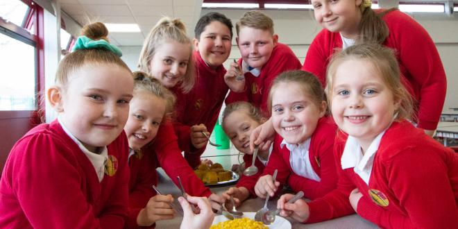 School pupils sat at a table eating sweetcorn