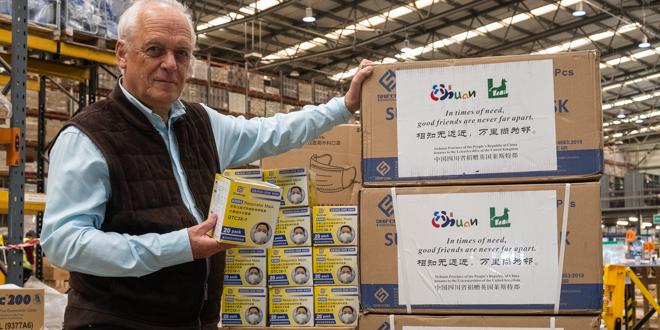 man stands next to boxes of boxed up surgical face masks