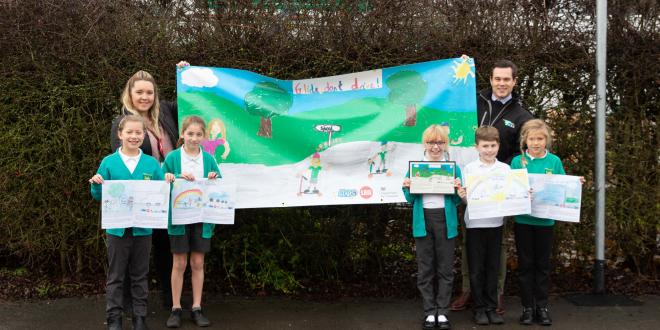Council staff reveal banner to fleckney primary school students outside school