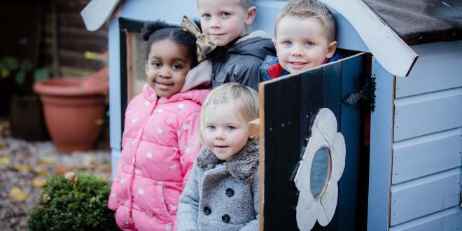 Children outside a play hut