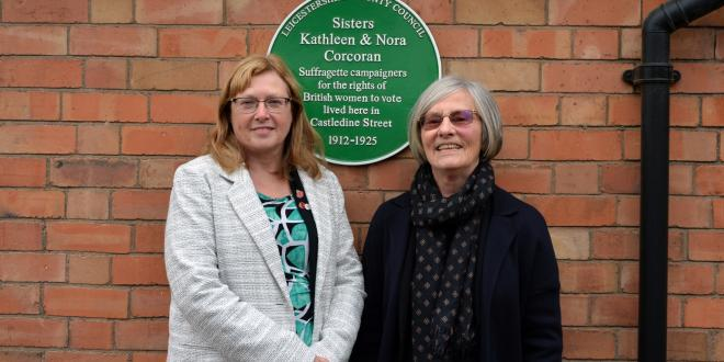 two women in front of green plaque