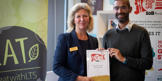 Two people standing with the Soil Association's Gold 'Food Served Here' catering award