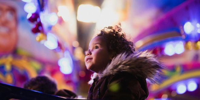 child looking at fair ground lights