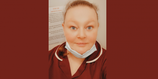 Photo of a lady in a care workers uniform working at her care home job