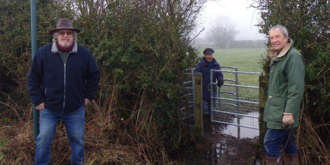 Two men and a woman stood socially distanced by a gate into a field