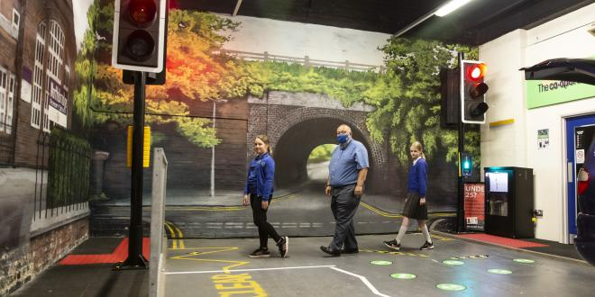 Two school girls cross a pedestrian road crossing with an adult wearing a covid face mask