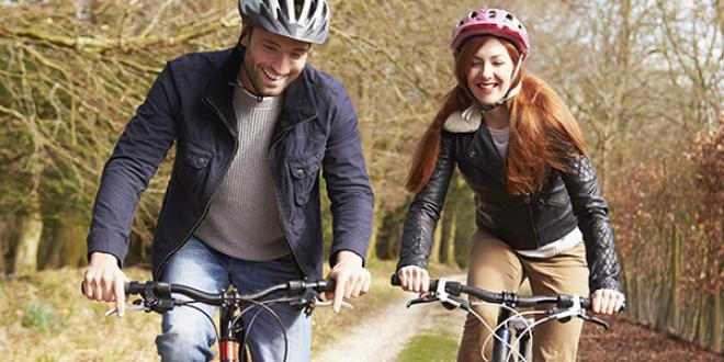 Two people riding bicycles on a woodland trail