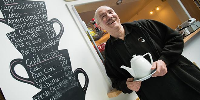man holding a tea pot, standing in a coffee shop